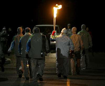 the-olympic-flame-being-carried-through-the-dark-and-cold